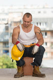 Tired Builder Resting On Brick Stock Photo