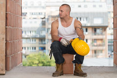 Tired Builder Resting On Brick Royalty Free Stock Photography