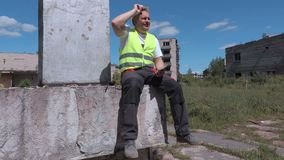 Tired builder sitting near abandoned apartment houses and using tablet stock video footage