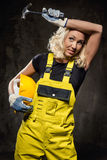 Tired builder woman. With hammer and helmet indoors Royalty Free Stock Photo