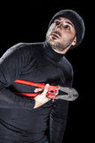Tired Burglar. A burglar wearing black clothes holding huge wire cutters over black background stock image