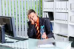Tired business man with head in hands is over-worked Royalty Free Stock Photos