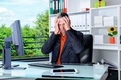 Tired business man lying with head in hands is over-worked Stock Photo