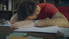 Tired business man lying on papers at table. Businessman sleeping on desk stock video