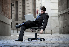 Tired Business Man sitting on Office Chair on Street sleeping Stock Photography