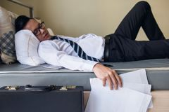 Tired Business man sleep and hold paper work Stock Photos