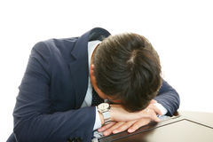 Tired business man sleeping at desk Royalty Free Stock Images