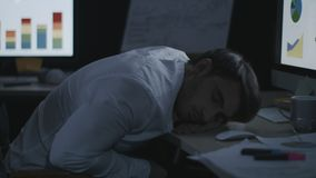 Tired business man sleeping on desk front computer screen in night office. Sleeping business analyst lying on computer table in dark office stock footage