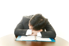 Tired business man sleeping at desk Royalty Free Stock Image