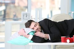 Tired business man sleeping among empty paper coffee cups. On worktable in office Stock Photo