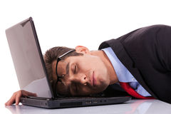 Tired business man sleeping on laptop Stock Images