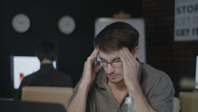 Tired business man touching head in dark office. Sad man working hard on laptop. stock video