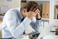 Tired business man at workplace in office holding his head in ha Royalty Free Stock Photos