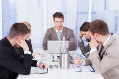 Tired business people in conference meeting. Young businessman looking at tired colleagues during conference meeting royalty free stock photos