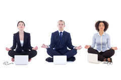 Tired business people sitting in yoga pose with laptops isolated Stock Photography