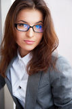 Tired business woman. Beautiful young business woman wearing glasses sitting relaxed at her office and looking at camera stock photo