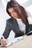 Tired business woman. Portrait of an adorable business woman working at her desk with paperwork royalty free stock image