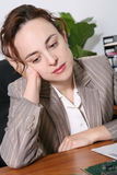 Tired Business Woman. A bored business woman leaning on her desk Royalty Free Stock Photo