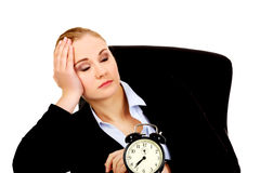 Tired business woman behind the desk with alarm clock Royalty Free Stock Image