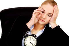 Tired business woman behind the desk with alarm clock Stock Photography