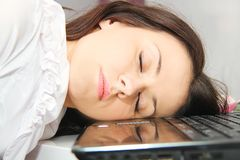 Tired business woman fell asleep next to a laptop Stock Image
