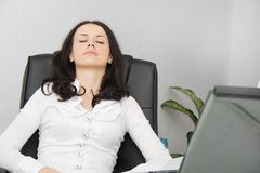 Tired business woman fell asleep next to a laptop Stock Images
