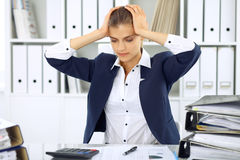 Tired business woman or female accountant with bills and paper folders in office Royalty Free Stock Photo