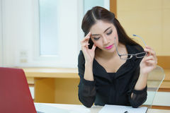Tired business woman having headache while working at desk.  Royalty Free Stock Photography
