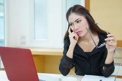 Tired business woman having headache while working at desk.  Stock Photos