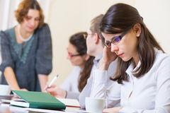 Tired business woman with headache at seminar Stock Images