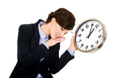 Tired business woman holding clock in hands. Royalty Free Stock Images