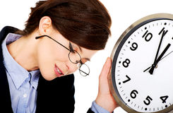 Tired business woman holding clock in hands. Stock Images