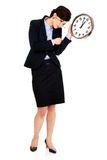 Tired business woman holding clock in hands. Royalty Free Stock Image