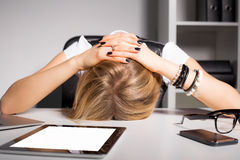 Tired business woman resting her head on desk Stock Photos
