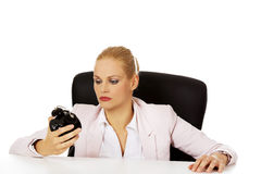 Tired business woman sitting behind the desk and holding alarm clock Stock Photos