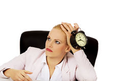 Tired business woman sitting behind the desk and holding alarm clock Royalty Free Stock Images