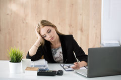 Tired business woman sitting at her working place Stock Photo