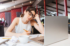 Tired business woman sitting and working with laptop in office Royalty Free Stock Images