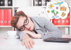 Tired business woman sleeping and dreaming about vacation in off. Tired business woman sleeping on the table and dreaming about vacation in office Stock Photography