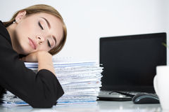 Tired business woman slleeping on heap of papers at her working Stock Images