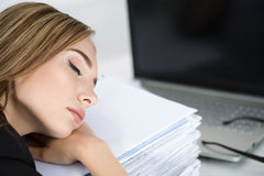 Tired business woman slleeping on heap of papers Stock Photos