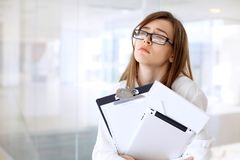 Tired business woman standing in the office.  Royalty Free Stock Photo