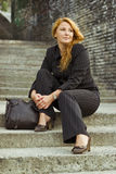Tired business woman in suit sitting on the stairs Royalty Free Stock Image