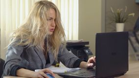 Tired business woman in suit works at the computer in office. Tired business woman in suit works at the computer in office stock video footage