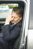 Tired businessman. A tired and frustrated looking forties businessman is sitting in his car with his hand against his head Stock Images