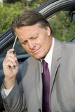 Tired businessman. A tired and frustrated looking forties businessman is sitting in his car with his hand against his head Royalty Free Stock Image