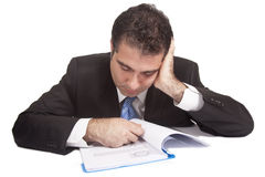Tired businessman. Falling asleep while reading documents in a file at a desk.  White background Stock Photos