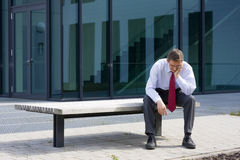 Tired businessman. Sitting on a bench in front of an office building Royalty Free Stock Images