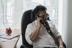 Tired businessman asian during a phone call sleeping on workplac. E at office desk surrounded by paperwork Royalty Free Stock Photo