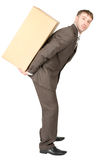 Tired businessman carrying heavy box on back. Tired young businessman carrying heavy box on back. Isolated on white background Royalty Free Stock Photo